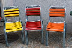 Ζωηρόχρωμες καρέκλες patio κήπων που συσσωρεύονται και που κλειδώνονται στοκ εικόνα