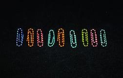 Ζωηρόχρωμες καρφίτσες γραφείων στο μαύρο υπόβαθρο Στοκ φωτογραφία με δικαίωμα ελεύθερης χρήσης
