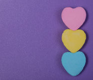 Ζωηρόχρωμες καρδιές. Καραμέλα τριών αγαπημένων πέρα από το πορφυρό υπόβαθρο Στοκ Εικόνες