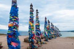 Ζωηρόχρωμες κορδέλλες στους ξύλινους πόλους στη λίμνη Baikal στη Σιβηρία στοκ φωτογραφία με δικαίωμα ελεύθερης χρήσης