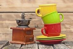 Ζωηρόχρωμες κούπες καφέ με το μύλο καφέ Στοκ Εικόνες