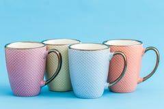Ζωηρόχρωμες κούπες καφέ στο μπλε υπόβαθρο Στοκ Εικόνες