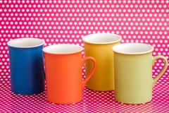 Ζωηρόχρωμες κούπες καφέ στο ρόδινο υπόβαθρο με τα άσπρα σημεία Στοκ εικόνα με δικαίωμα ελεύθερης χρήσης