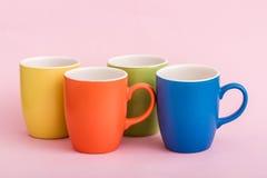 Ζωηρόχρωμες κούπες καφέ στο ρόδινο υπόβαθρο Στοκ Εικόνα
