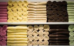 Ζωηρόχρωμες πετσέτες με το ψάθινο καλάθι στο ράφι του υποβάθρου ραφιών Στοκ Εικόνες