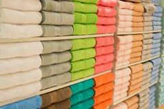 Ζωηρόχρωμες πετσέτες με το ψάθινο καλάθι στο ράφι του υποβάθρου ραφιών Στοκ φωτογραφίες με δικαίωμα ελεύθερης χρήσης