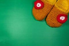 Ζωηρόχρωμες πλεκτές παντόφλες σε ένα πράσινο υπόβαθρο στοκ εικόνες με δικαίωμα ελεύθερης χρήσης