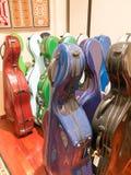 Ζωηρόχρωμες πολύχρωμες περιπτώσεις μεταφοράς βιολοντσέλων που στέκονται στην επίδειξη Στοκ Εικόνες