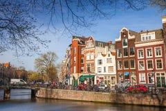 Ζωηρόχρωμες προσόψεις σπιτιών την ηλιόλουστη ημέρα καναλιών την άνοιξη στο Άμστερνταμ Στοκ Εικόνες