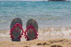 Ζωηρόχρωμες πτώσεις κτυπήματος παραλιών σε μια άμμο κοντά στη θάλασσα Παντόφλες γυναικών Στοκ εικόνες με δικαίωμα ελεύθερης χρήσης