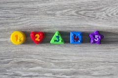 Ζωηρόχρωμες πλαστικές μορφές με τους αριθμούς σε ένα ξύλινο υπόβαθρο Στοκ φωτογραφίες με δικαίωμα ελεύθερης χρήσης