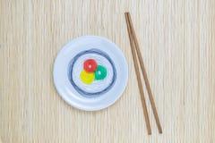 Ζωηρόχρωμες σειρές με μορφή σουσιών στο άσπρο πιάτο και ραβδιών που απομονώνονται στο μπεζ υπόβαθρο χαλιών αχύρου μπαμπού Στοκ Εικόνα