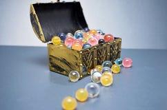 Ζωηρόχρωμες σφαίρες που ανατρέπουν από ένα στήθος θησαυρών με το bokeh Στοκ Εικόνες