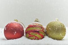 Ζωηρόχρωμες σφαίρες Χριστουγέννων στο χιονώδες υπόβαθρο στοκ εικόνα