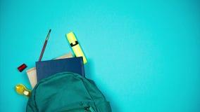 Ζωηρόχρωμες σχολικές προμήθειες που κινούνται από τη σχολική τσάντα στο μπλε υπόβαθρο Κίνηση στάσεων απόθεμα βίντεο