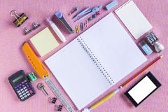 Ζωηρόχρωμες σχολικές προμήθειες που οργανώνονται από τον τύπο γύρω από το βιβλίο σημειώσεων ανοικτό στην κενή σελίδα που τακτοποι Στοκ εικόνα με δικαίωμα ελεύθερης χρήσης