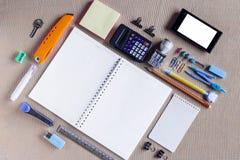 Ζωηρόχρωμες σχολικές προμήθειες που οργανώνονται από τον τύπο γύρω από το βιβλίο σημειώσεων ανοικτό στην κενή σελίδα που τακτοποι Στοκ Εικόνες