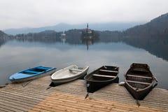 Ζωηρόχρωμες τέσσερις ξύλινες βάρκες κωπηλασίας στο θαυμάσιο φυσικό νησί με την εκκλησία στην καθαρή λίμνη που αιμορραγείται Στοκ Εικόνα