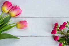 Ζωηρόχρωμες τουλίπες με τα μικροσκοπικά τριαντάφυλλα στον ξύλινο πίνακα Στοκ Εικόνα