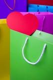 Ζωηρόχρωμες τσάντες αγορών εγγράφου με την κόκκινη καρδιά Στοκ Εικόνες