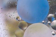 Ζωηρόχρωμες φυσαλίδες πετρελαίου σε ένα αφηρημένο υπόβαθρο επιφάνειας νερού με το κόκκινο στοκ εικόνες