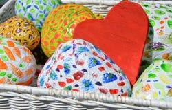 Ζωηρόχρωμες χρωματισμένες πέτρες και καρδιά αγάπης στο άσπρο καλάθι Στοκ φωτογραφία με δικαίωμα ελεύθερης χρήσης