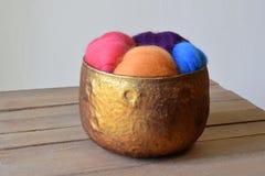 Ζωηρόχρωμη ίνα μαλλιού προβάτων σε ένα κύπελλο γυαλιού χαλκού σε ένα ξύλινο χαλί Στοκ Εικόνα