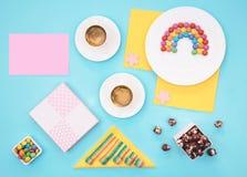 Ζωηρόχρωμη ακόμα ζωή με τα γλυκά και παρόν στο μπλε υπόβαθρο Στοκ εικόνα με δικαίωμα ελεύθερης χρήσης