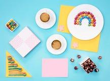 Ζωηρόχρωμη ακόμα ζωή με τα γλυκά και παρόν στο μπλε υπόβαθρο Στοκ Φωτογραφία