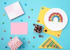 Ζωηρόχρωμη ακόμα ζωή με τα γλυκά και παρόν στο μπλε υπόβαθρο Στοκ Φωτογραφίες