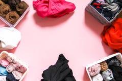 Ζωηρόχρωμη αποθήκευση ενδυμάτων στην εγχώρια ντουλάπα Διαφορετικά στοιχεία ιματισμού στα πλαστικά και υφαντικά κιβώτια στοκ φωτογραφίες