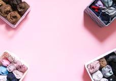 Ζωηρόχρωμη αποθήκευση ενδυμάτων στην εγχώρια ντουλάπα Στοιχεία του ιματισμού στα υφαντικά κιβώτια στο μαλακό ρόδινο υπόβαθρο στοκ φωτογραφίες με δικαίωμα ελεύθερης χρήσης