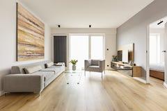 Ζωηρόχρωμη ζωγραφική επάνω από τον καναπέ στο εσωτερικό καθιστικών με το armcha στοκ εικόνες με δικαίωμα ελεύθερης χρήσης