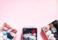 Ζωηρόχρωμη κάθετη αποθήκευση ενδυμάτων στην ντουλάπα Στοιχεία του ιματισμού στα πλαστικά και υφαντικά κιβώτια στο μαλακό ρόδινο υ στοκ εικόνα