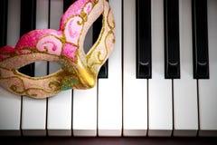 Ζωηρόχρωμη και όμορφη μάσκα προσώπου στο γραπτό υπόβαθρο κλειδιών πληκτρολογίων πιάνων Στοκ φωτογραφίες με δικαίωμα ελεύθερης χρήσης