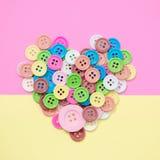 Ζωηρόχρωμη καρδιά κουμπιών στο υπόβαθρο χρώματος στοκ εικόνες