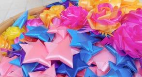 Ζωηρόχρωμη κορδέλλα που διαμορφώνει τα αστέρια και τα λουλούδια Στοκ Εικόνες