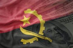 Ζωηρόχρωμη κυματίζοντας εθνική σημαία της Ανγκόλα σε ένα αμερικανικό υπόβαθρο χρημάτων δολαρίων Στοκ Φωτογραφία
