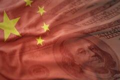 Ζωηρόχρωμη κυματίζοντας εθνική σημαία της Κίνας σε ένα αμερικανικό υπόβαθρο χρημάτων δολαρίων Στοκ Εικόνες