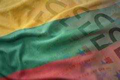 Ζωηρόχρωμη κυματίζοντας εθνική σημαία της Λιθουανίας σε ένα ευρο- υπόβαθρο τραπεζογραμματίων χρημάτων Στοκ φωτογραφίες με δικαίωμα ελεύθερης χρήσης