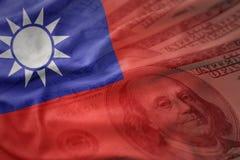 Ζωηρόχρωμη κυματίζοντας εθνική σημαία της Ταϊβάν σε ένα αμερικανικό υπόβαθρο χρημάτων δολαρίων Στοκ Φωτογραφία