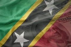 Ζωηρόχρωμη κυματίζοντας εθνική σημαία του St Kitts and Nevis σε ένα αμερικανικό υπόβαθρο χρημάτων δολαρίων Στοκ εικόνα με δικαίωμα ελεύθερης χρήσης