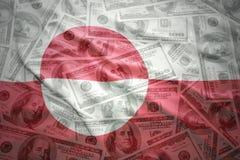 Ζωηρόχρωμη κυματίζοντας greenlandic σημαία σε ένα υπόβαθρο χρημάτων δολαρίων στοκ φωτογραφίες