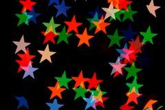 Ζωηρόχρωμη μορφή αστεριών boke στο σκοτεινό υπόβαθρο Στοκ Εικόνες