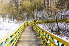 Ζωηρόχρωμη ξύλινη διάβαση μια χειμερινή ημέρα σε ένα χιονώδες πάρκο με το δάσος που έχει τους διάφορους τύπους υπαίθριων εννοιών  Στοκ Εικόνες