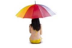 ζωηρόχρωμη ομπρέλα συνεδρίασης κάτω από τη γυναίκα Στοκ Εικόνες