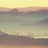 Ζωηρόχρωμη πτώση παγώματος Τοπίο λόφων βουνών φθινοπώρου της Misty Φιλτραρισμένη εικόνα με τη διαγώνια επεξεργασμένη ζωηρή επίδρα Στοκ Εικόνα
