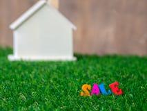 Ζωηρόχρωμη πώληση κειμένων στο μέτωπο του ξύλινου προτύπου σπιτιών που τοποθετείται σε μια πράσινη χλόη σύσταση σπιτιών eco σχεδί στοκ φωτογραφίες με δικαίωμα ελεύθερης χρήσης