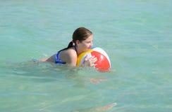 Ζωηρόχρωμη σφαίρα χαλάρωσης κοριτσιών στον όμορφο ωκεανό Στοκ Εικόνες