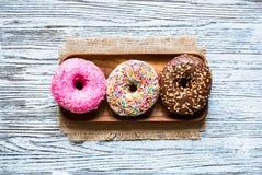 Ζωηρόχρωμη σύνθεση προγευμάτων Donuts με τις διαφορετικές μορφές χρώματος στοκ εικόνες